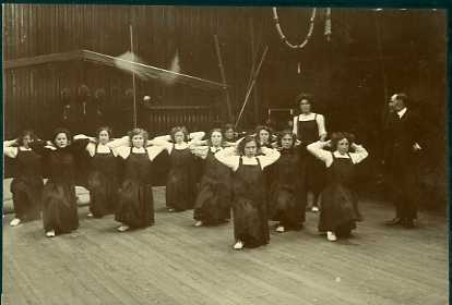 Girls' gymnastics class; physical exercises. Teacher and WJ Gibson standing at side.