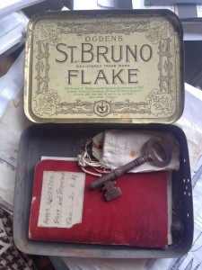 Tobacco tin containing a notebook and a key